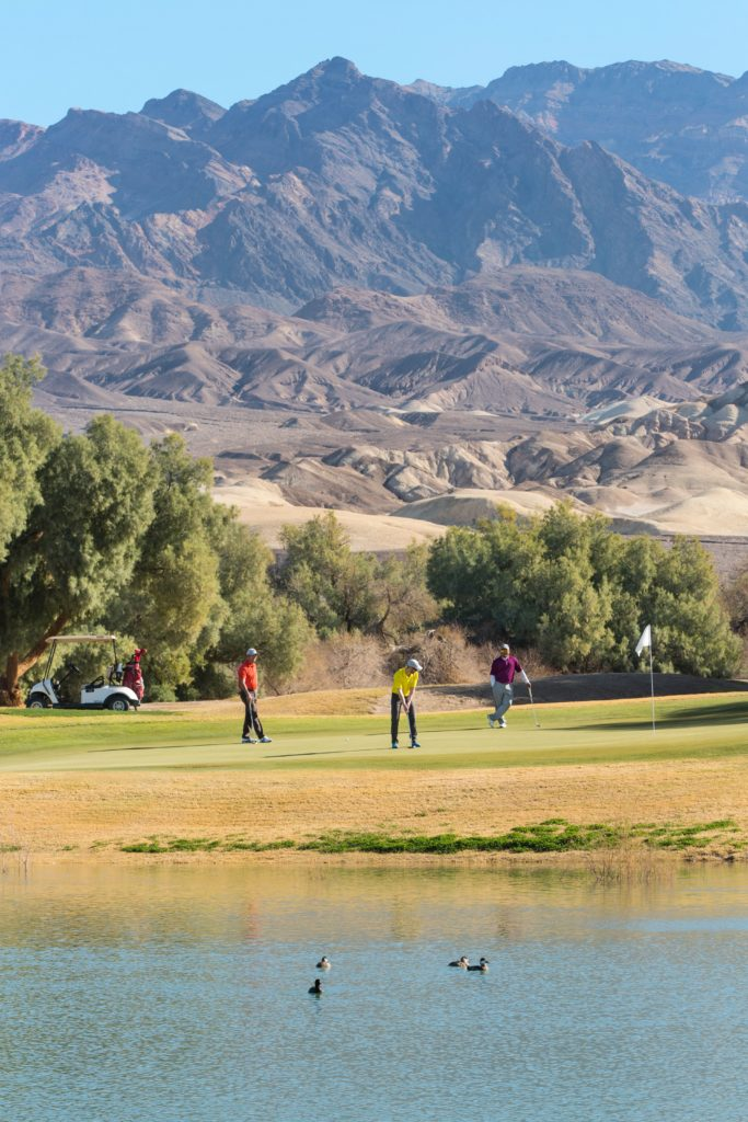 Golfers putting in the green on the 7th hole of Furnace Creek Golf Course