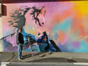 Man next to mural of a horse